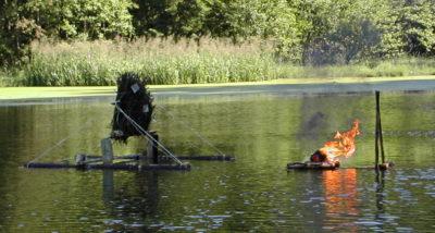 Pokus s hořící lodičkou. Je ze břehu tlačena dlouhými pruty.